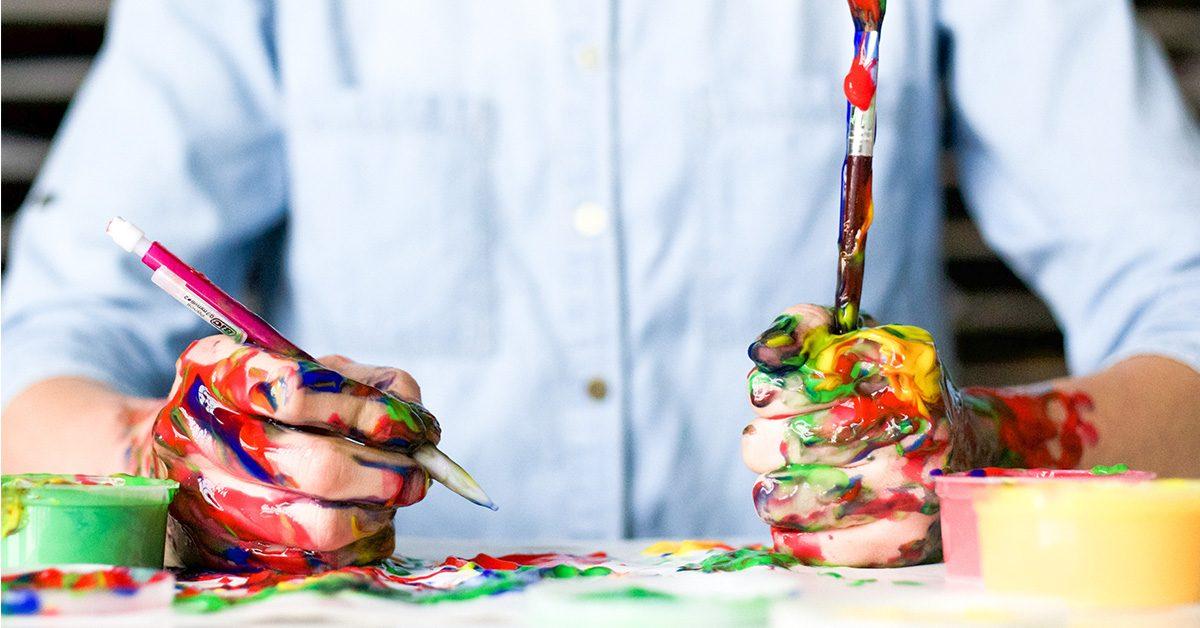 Dłonie poplamione kolorowymi farbami