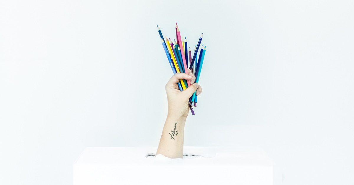 Kolorowe kredki w dłoni